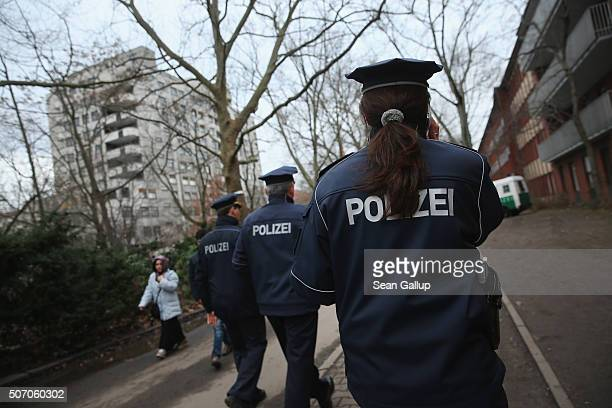 Police walk outside the the Central Registration Office for Asylum Seekers of the State Office for Health and Social Services the day after a young...