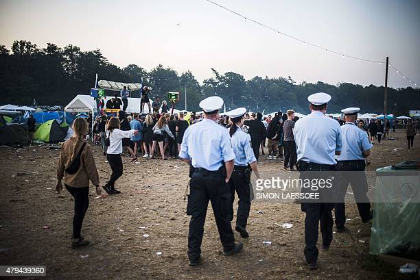 Police walk over the festival grounds early in the morning during the annual Roskilde Festival in Roskilde Denmark on July 4 2015 This year's...