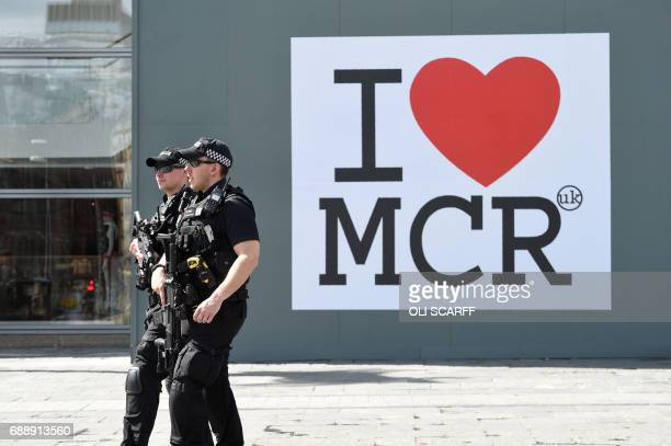 Police walk past a huge message of support following the Manchester attack outside the Manchester Arena Complex in Manchester on May 27 2017 British...