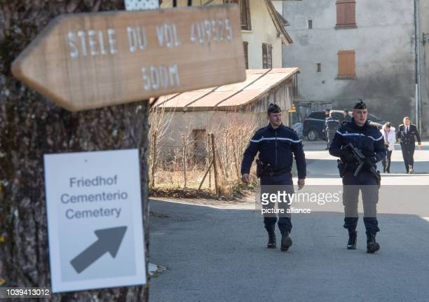 Police walk past signs pointing to the memorial and cemetery ahead of the memorial for the victims of the Germanwings flight 4U9525 plane crash in Le...