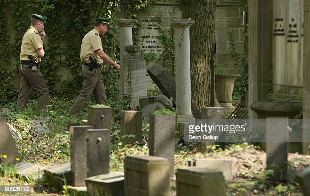 Police walk through a section of Berlin's biggest Jewish cemetery where at least 30 graves were vandalized on April 30 2008 in Berlin Germany In most...