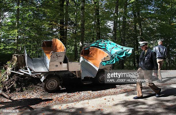 Police walks by a damaged horse carriage on October 8 2012 in Hohenschwangau near the Neuschwanstein Castle in Bavaria Eight people including four...