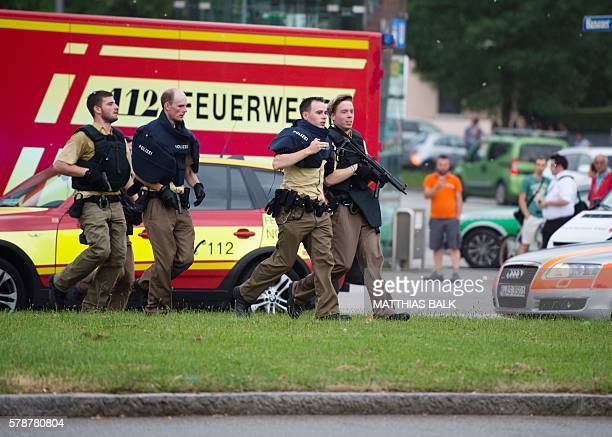 Police walks near a shopping mall amid a shooting on July 22 2016 in Munich Several people were killed on Friday in a shooting rampage by a lone...
