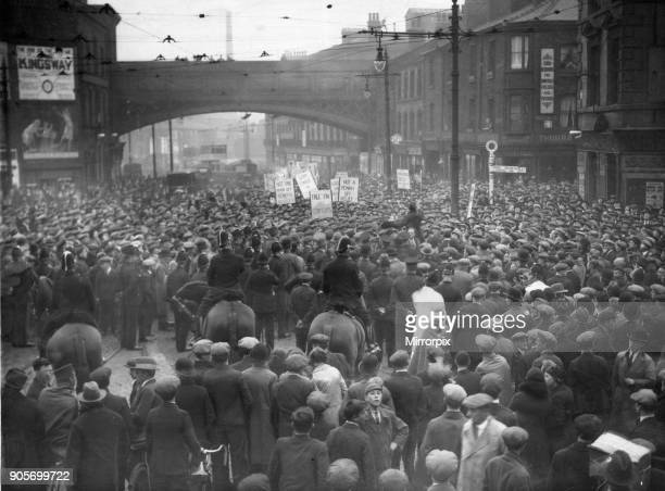 Police watch a demonstration of unemployed workers organised by the National Unemployed Workers Movement march down London Road Manchester to protest...