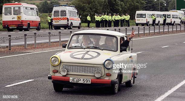 Police watch a demonstrators travel in a Trabant vehicle on the A9 road into Auchterarder on July 6 2005 near Gleneagles The G8 summit where...