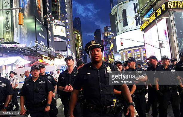 Police watch activists protest in Times Square in response to the recent fatal shootings of two black men by police July 7 2016 in New York City...