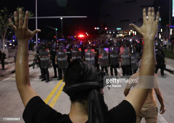 Police watch as demonstrators block a roadway while protesting against police brutality and the death of George Floyd on May 31 2020 in Miami Florida...