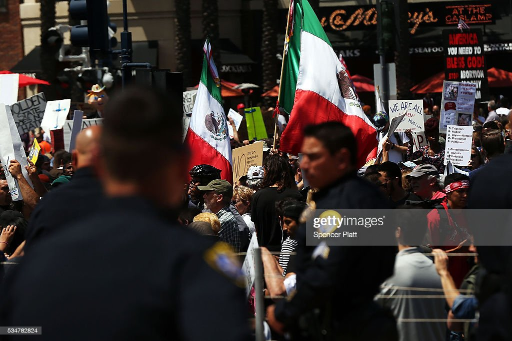 Police watch as demonstrators protest outside of an arena where the presumptive Republican presidential candidate Donald Trump is holding a rally in San Diego on May 27, 2016 in Fresno, California. Trump is on a western campaign trip which saw stops in North Dakota and Montana yesterday and two more in California today.