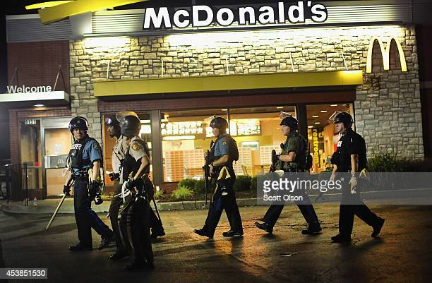 Police watch as demonstrators protest the killing of teenager Michael Brown on August 19 2014 in Ferguson Missouri Brown was shot and killed by a...