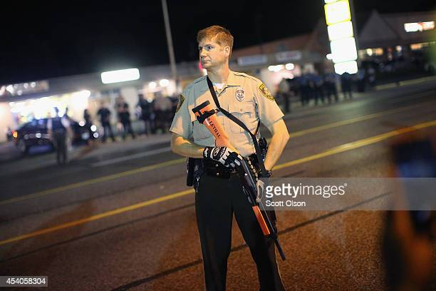 FERGUSON MO AUGUST 23 Police watch as demonstrators protest the shooting death of Michael Brown along West Florissant Avenue on August 23 2014 in...