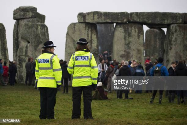 Police watch as druids pagans and revellers gather in the centre of Stonehenge hoping to see the sun rise as they take part in a winter solstice...
