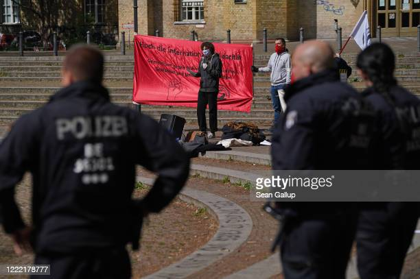 Police watch as leftwing protesters wearing protective face masks demonstrate on Mariannenplatz while maintaining social distancing on May Day during...