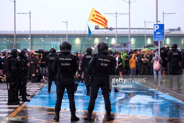 Police watch as protestors block the Barcelona Airport access in a protest following the sentencing of nine Catalan separatist leaders on October 14,...
