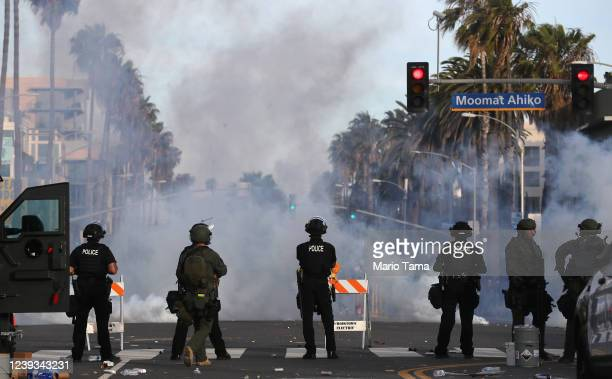 Police watch as tear gas is deployed during demonstrations in the aftermath of George Floyd's death on May 31 2020 in Santa Monica California...