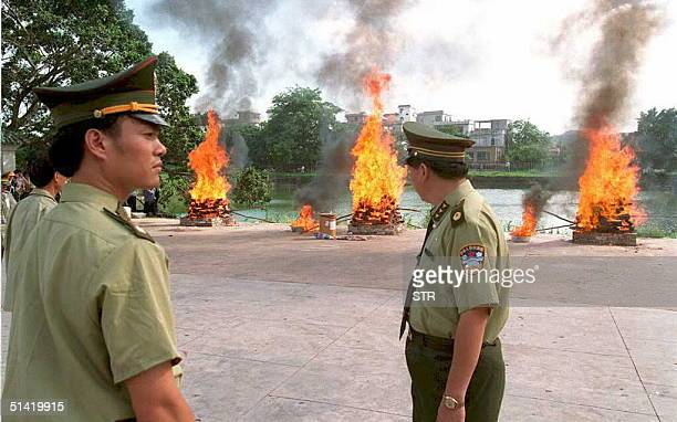 Police watch burning opium heroin and other drugs 25 June in Humen southern Chinese Guangdong province at the Opium War Museum the site of the...