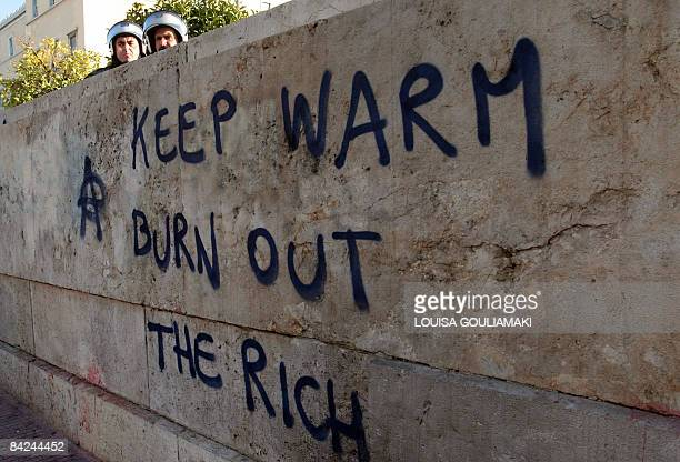 Police watch demonstrators over a wall with an anarchist graffiti at the Greek parliament during a proimmigrant demonstraton in Athens on January 11...
