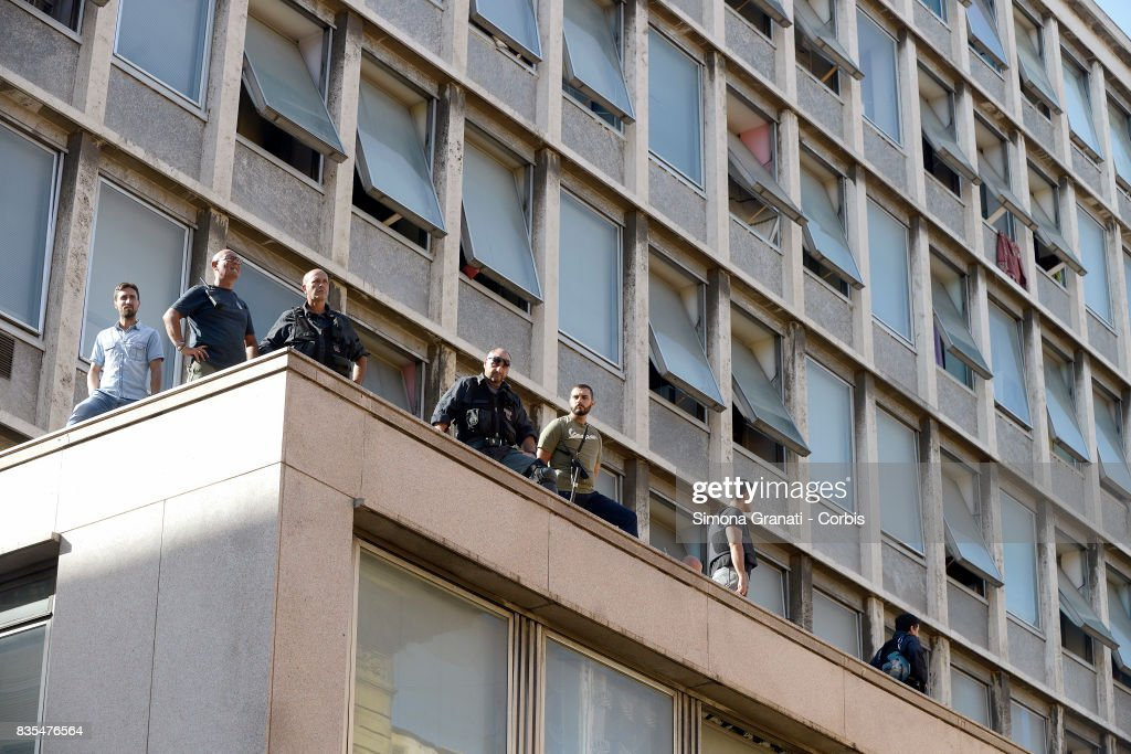 Police watch from rooftops during the evacuation of approx 500 Eritrean and Somali refugees form an occupied building in Piazza Indipendenza where approx 500 Eritrean and Somali refugees were living on August 19, 2017 in Rome, Italy.