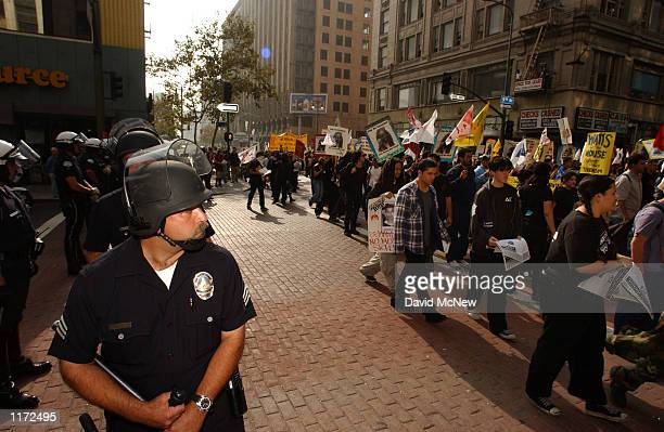 Police watch marchers during the October 22nd Coalition's sixth annual national protest against police brutality October 22 2001 in Los Angeles CA...