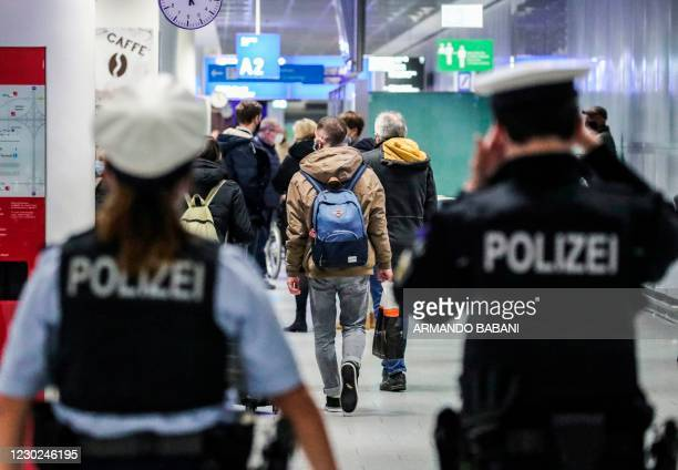 Police watch passengers arriving at Frankfurt International Airport in Frankfurt am Main, western Germany, on December 21 amid the ongoing novel...
