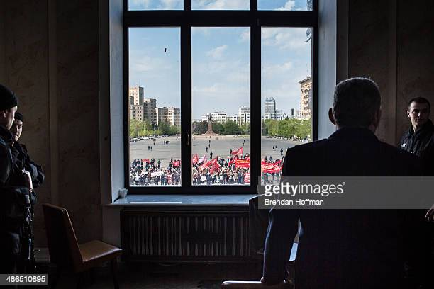 Police watch proRussian separatists holding a rally outside from a window in the regional administration building on April 24 2014 in Kharkiv Ukraine...
