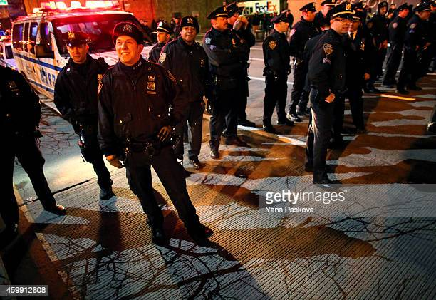 Police watch protesters stand together on the West Side Highway December 3 2014 in New York Protests began after a Grand Jury decided to not indict...