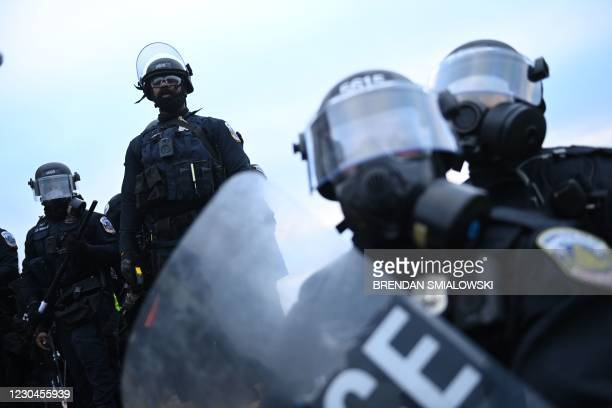 Police watch supporters of US President Donald Trump at the US Capitol in Washington, DC, on January 6, 2021. - Demonstrators breeched security and...