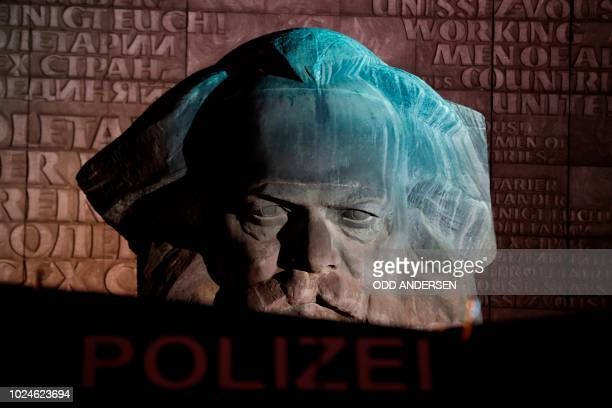 Police Water Cannon is seen in front of a sculpture of Karl Marx where Right-wing demonstrators staged a rally on August 27, 2018 in Chemnitz,...