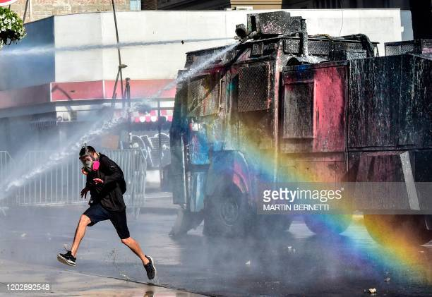 Police water cannon sprays on a demonstrator during a protest against Chilean President Sebastian Pinera's government in Vina del Mar, on February 23...