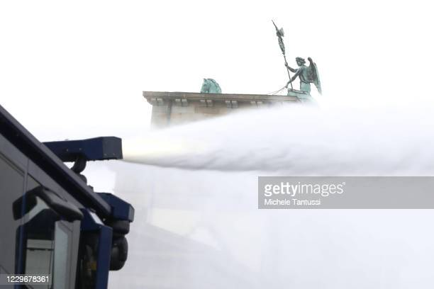 Police water cannon vehicle sprays in front of the Brandenburg Gate during a protest next to the Reichstag against modifications to a law called the...