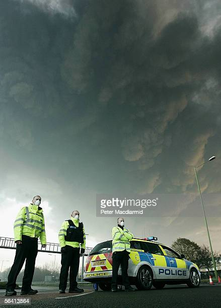 Police wearing face masks man a roadblock as smoke rises from the a fire at the Buncefield fuel depot on December 11 2005 in Hemel Hemstead England...