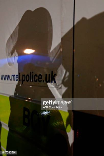 Police wearing helmets cast a shadow on a police van outside the stadium as the kick off is delayed due to crowd safety issues ahead of the UEFA...