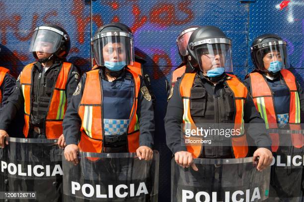 Police wearing protective masks stand guard at the Palacio of Bellas Artes during a rally on International Women's Day in Mexico City Mexico on...