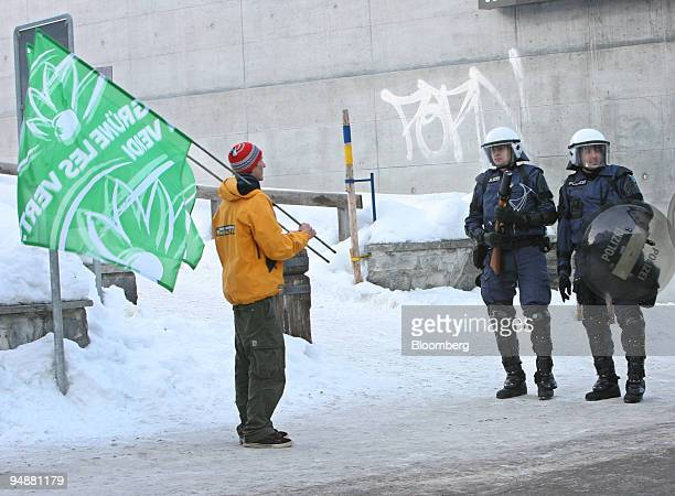 Police wearing riot gear stop a demonstrator from approaching the Congress Center where the World Economic Forum is being held in Davos Switzerland...
