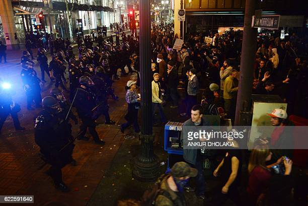 Police wearing riot gear watch as demonstrators protest against Donald Trump's US presidential election victory at City Hall in Portland on November...