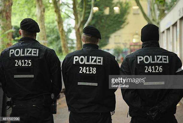 Police who have turned their backs in order to hide their faces from cameras stand guard at the GerhartHauptmannSchule school in Kreuzberg district...