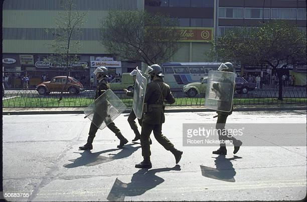 Police with riot control gear on hand during AntiPinochet government demonstrationsenched fists also police wriot control gear on hand