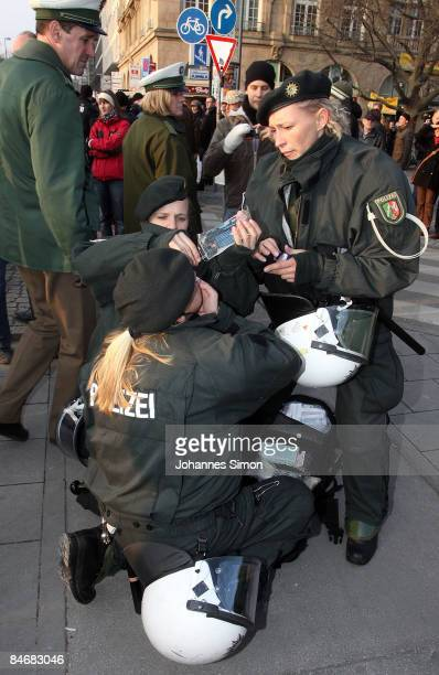 A police woman hurt by pepper spray is medicated by colleagues during a demonstration against the Munich Security Conference and the NATO policy on...