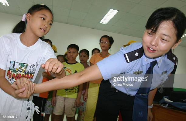 A police woman instructs a young girl selfdefence skills during an educational activity on August 24 2005 in Nanning of Guangxi Zhuang Autonomous...