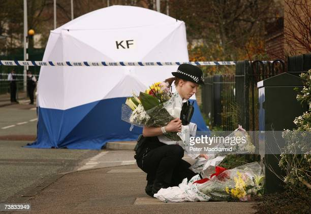 A police woman places floral tributes near a tent covering the murder scene in Leytonstone on April 7 2007 in northeast London England Paul Erhahon...
