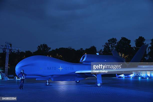 A police woman poses for a snapshot from colleagues next to an illuminated NATO Global Hawk reconaissance drone outside the PGE National Stadium site...