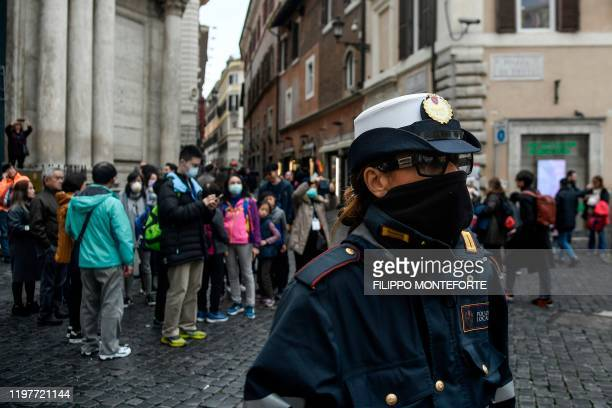 A police woman protects her face with a scarf while standing guard by the Trevi fountain where tourists wear protective respiratory masks in downtown...
