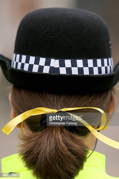 A police woman wears a yellow ribbon in her hair during the funeral service of teenage cancer fundraiser Stephen Sutton outside Lichfield Cathedral...
