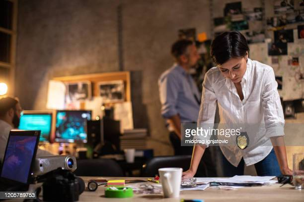 police woman working late alongside her colleagues to solve murder case late at night at office - police chief stock pictures, royalty-free photos & images