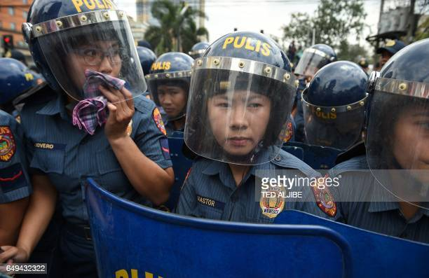 TOPSHOT Police women holding truncheons stand guard as women's group Gabriela hold a rally to celebrate International Women's Day near the US embassy...