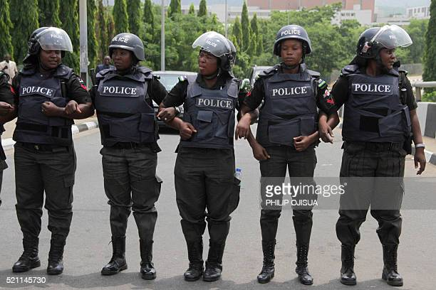 Police women link arms to stop protesters from advancing to the presidency as people gather to press for the release of the missing Chibok...