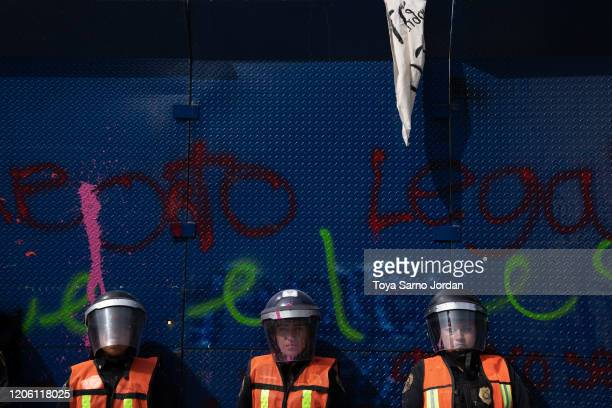 Police women stand guard during a rally on International Women's Day on March 8 2020 in Mexico City Mexico