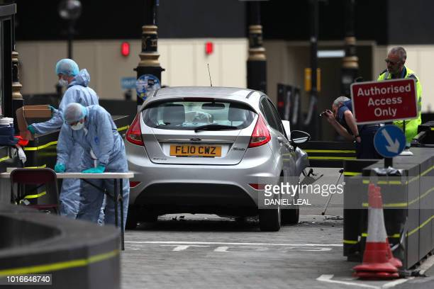 Police work around a silver Ford Fiesta car that was driven into a barrier at the Houses of Parliament in central London on August 14 2018 A car...