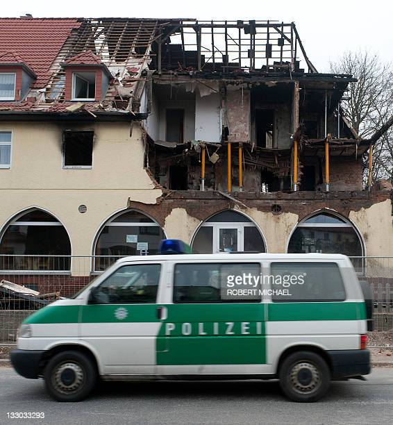 A policecar drives by the debris of the burnt house of 36years old suspect Beate Z in Zwickau eastern Germany on November 16 2011 Beate Z a militant...