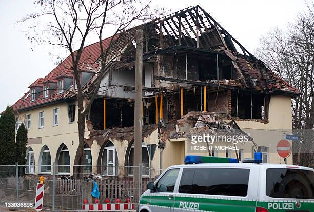 A policecar stands in front of the debris of the burnt house of 36years old suspect Beate Z in Zwickau eastern Germany on November 16 2011 Beate Z a...
