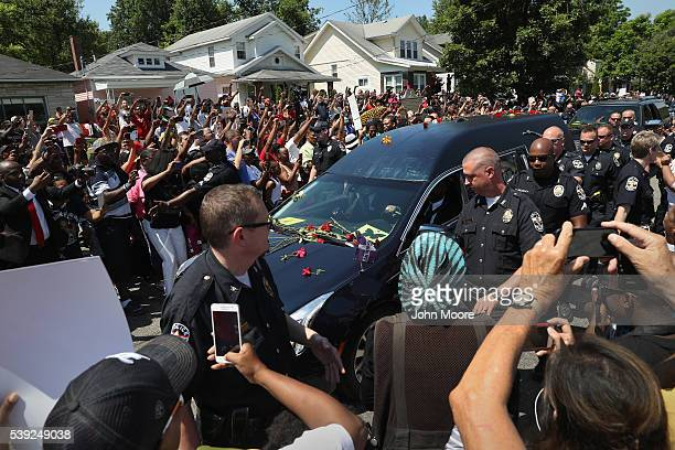 A policeescorted hearse carrying the body of Muhammed Ali passes by his childhood home on June 10 2016 in Louisville Kentucky The funeral possession...